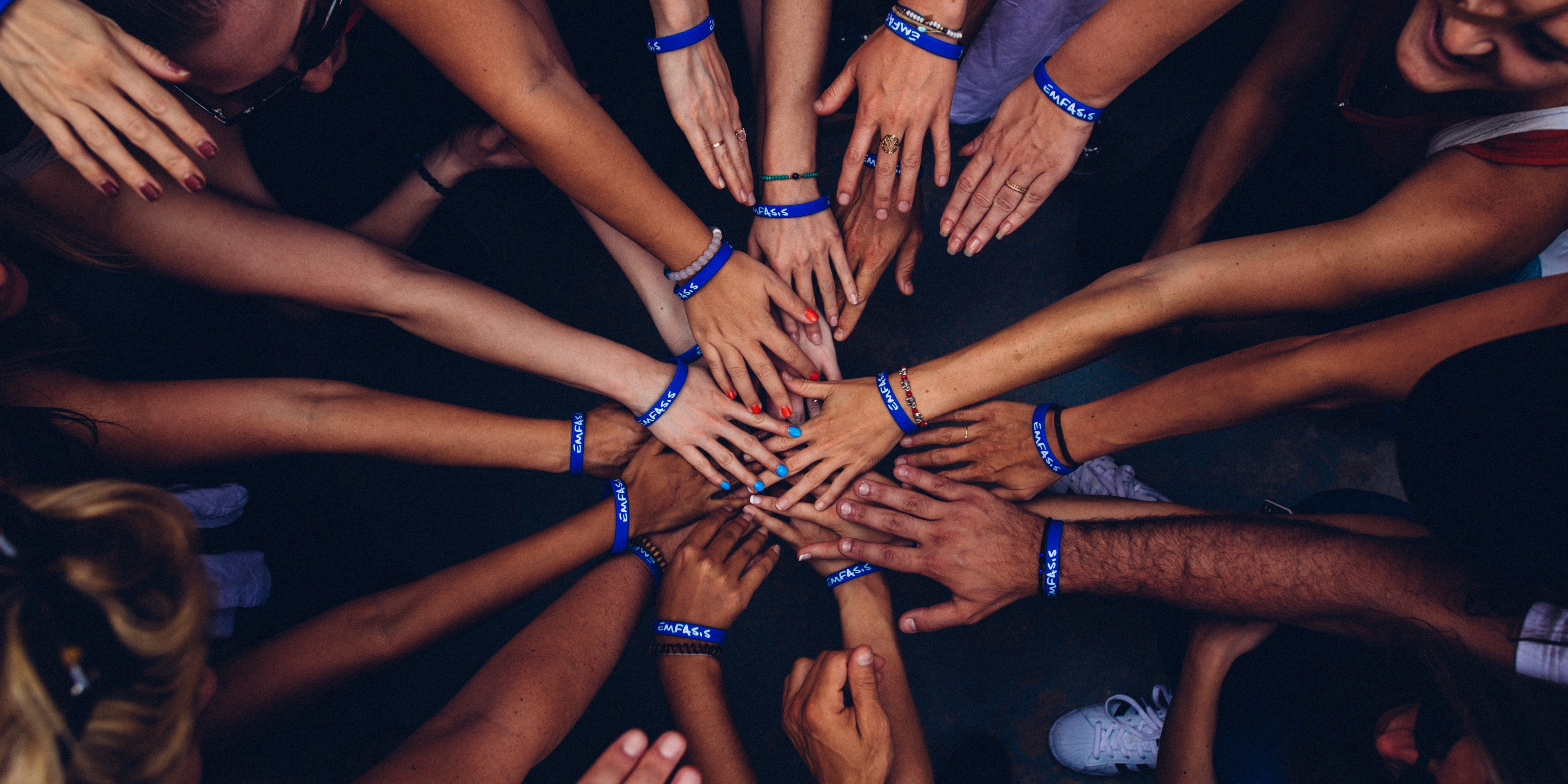 Group of people huddling with their hands in the middle