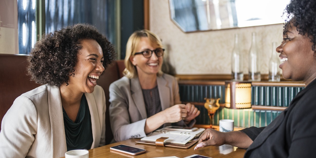 Women laughing with two coworkers in coffee shop