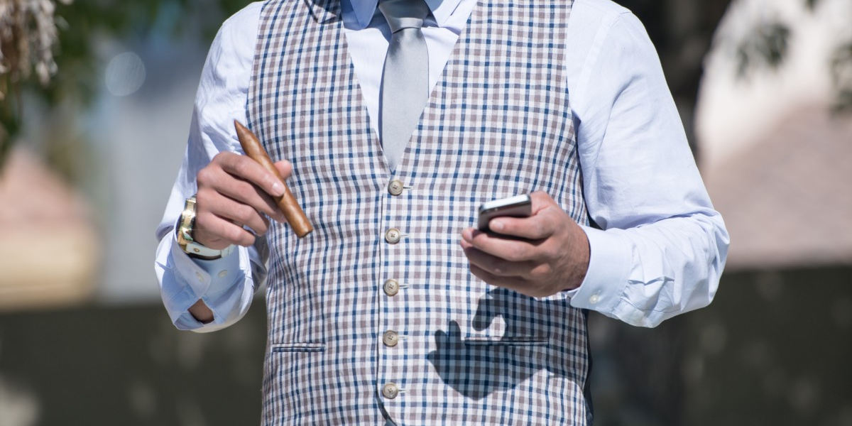 Businessman in waistcoat holding phone and cigar