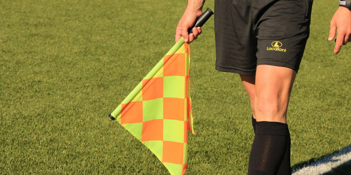 Close up of football linesman holding flag down