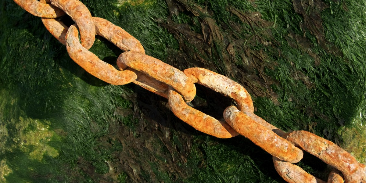 Rusted chain links help above green grass