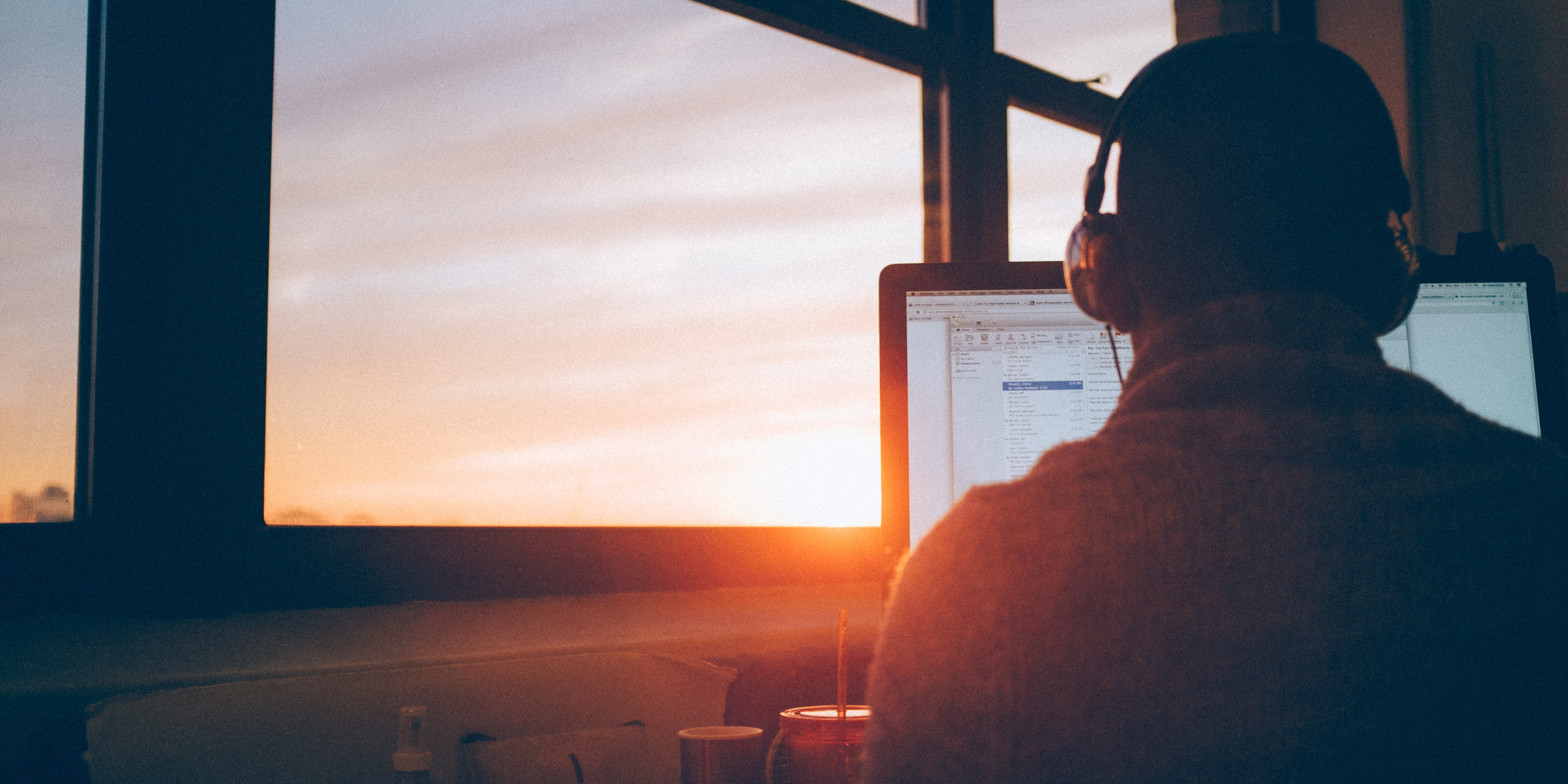 Man wearing headphones and looking at computer screen while sun sets