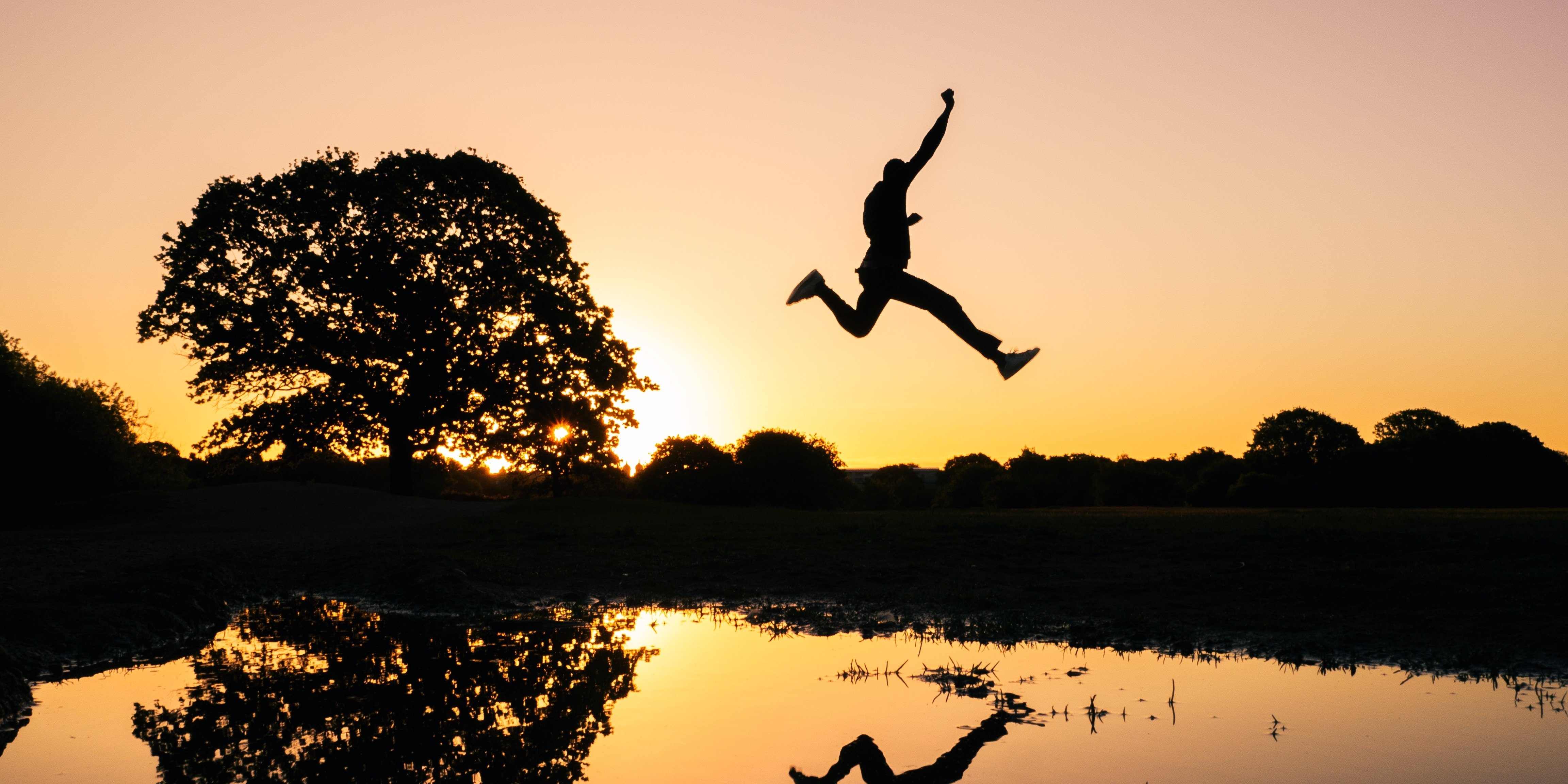 Silhouette of person jumping over water as sun sets