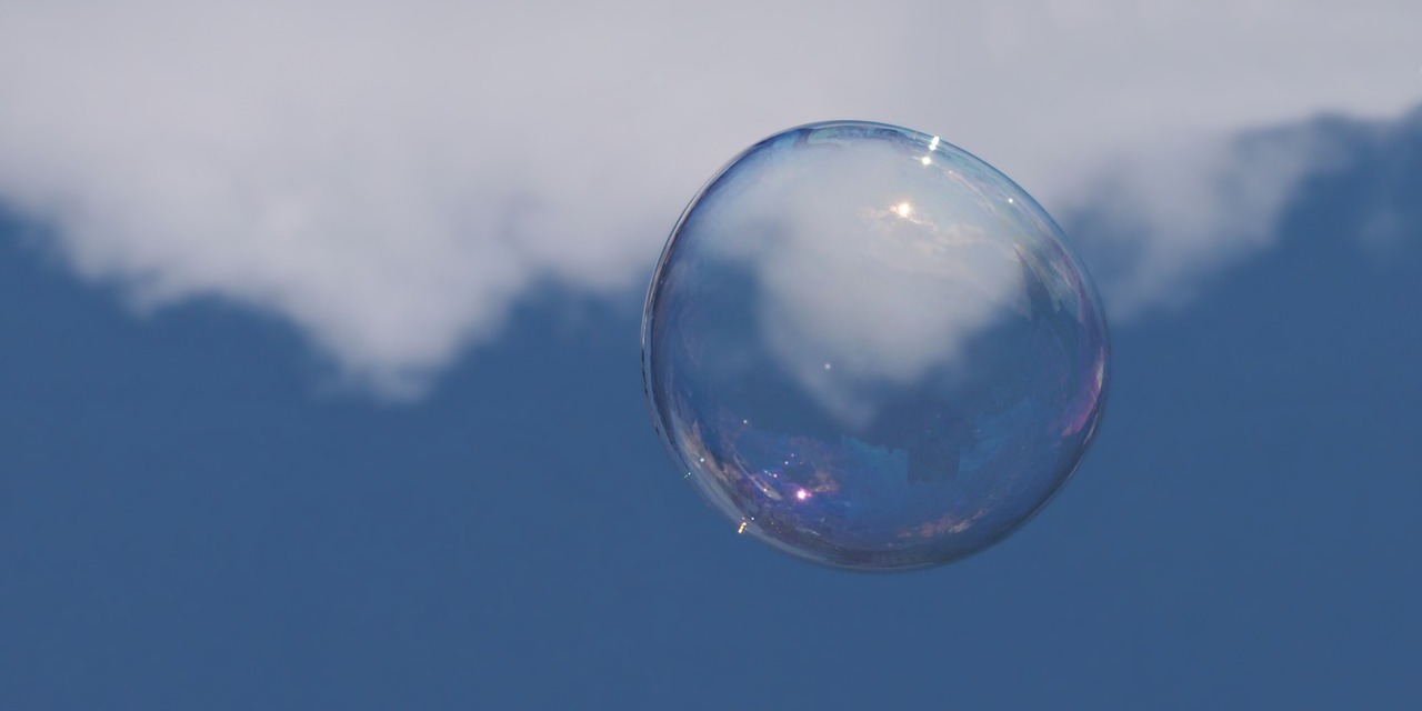 Soap bubble floating in sky over cloud